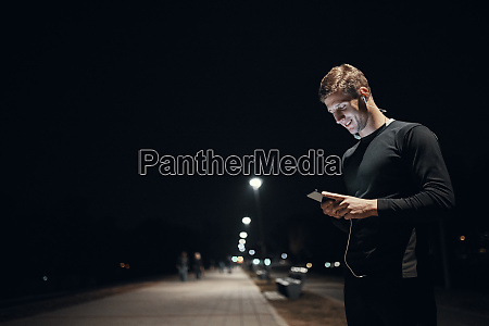 sportive young man with smartphone and