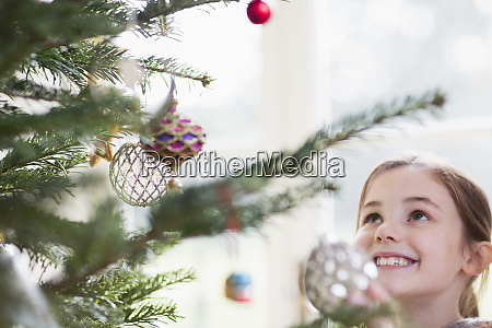 smiling girl looking up at ornaments