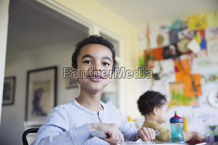 portrait confident boy eating at dining