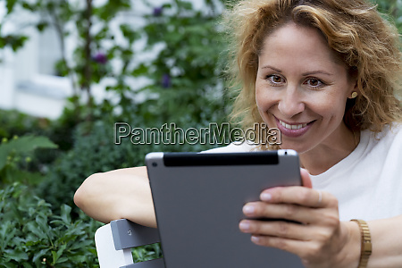 portrait of smiling woman using digital