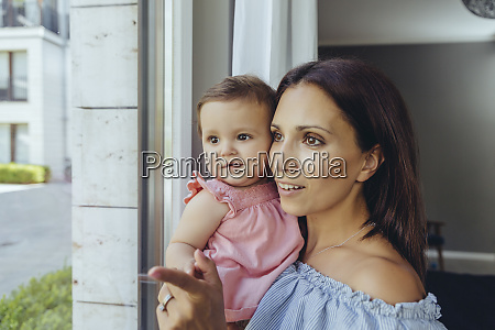 smiling mother looking out of window
