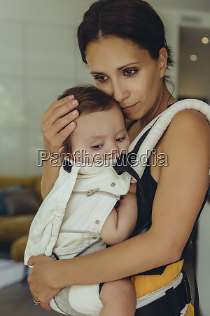 mother carrying her baby girl in