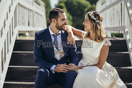happy bridal couple sitting on stairs