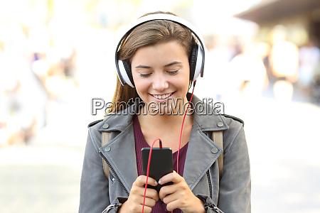 adolescente sonriente escuchando musica en un