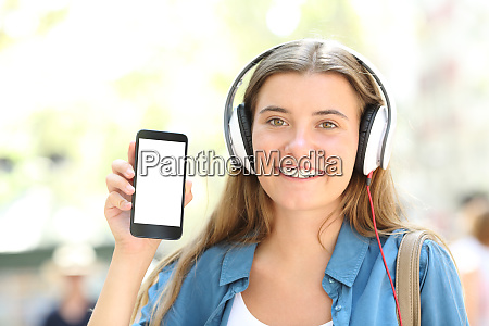 girl with headphones showing blank smart