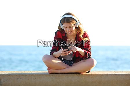 adolescente navegando canciones en el telefono