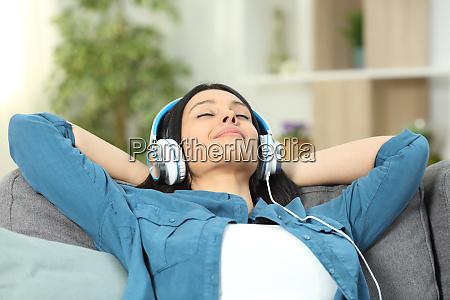 mujer relajada descansando escuchando musica en