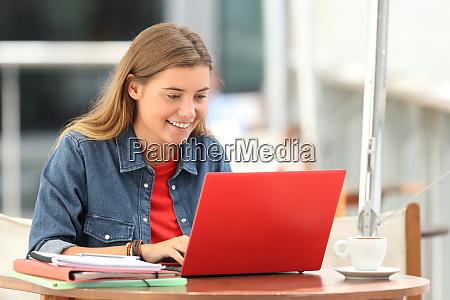 estudiante feliz escribiendo en una computadora