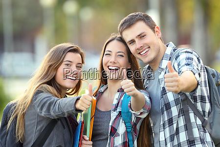 tres estudiantes felices con pulgar hacia
