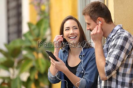 pareja feliz compartiendo musica en una