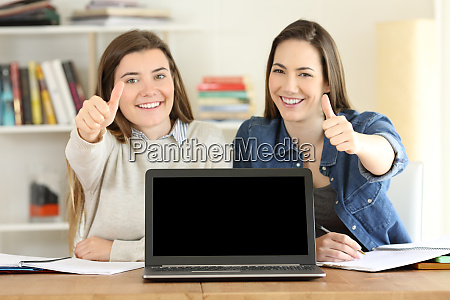 two students showing a blank laptop