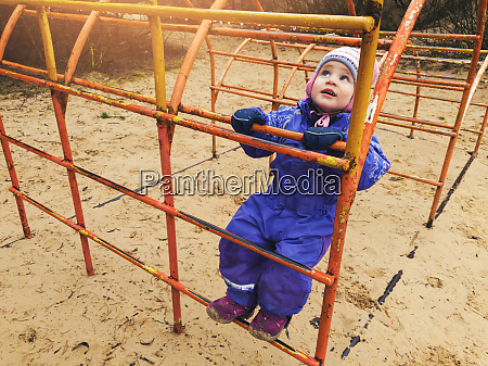little child climbing on ladder at