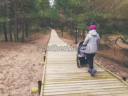 woman with stroller walking on wooden