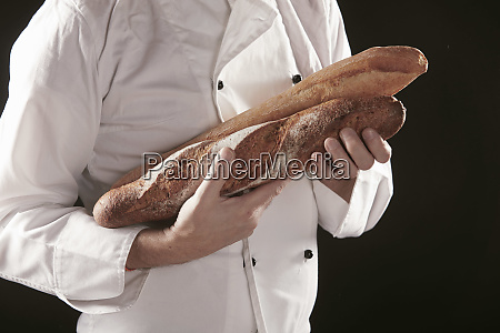 baker in white holding two baguettes