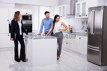 real estate agent showing refrigerator in