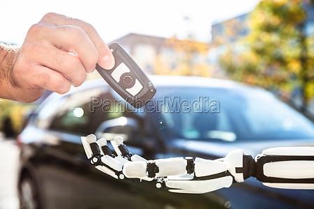 man giving car key to robot