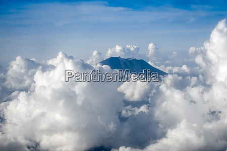 airplane flying above mount agung volcano