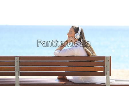 mujer relajada en un banco escuchando