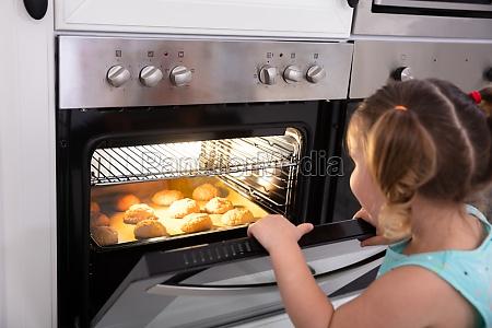 chica horneando galletas en horno