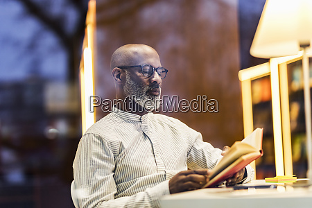 portrait of man reading book at
