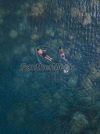 ninyos asiaticos snorkeling en el oceano
