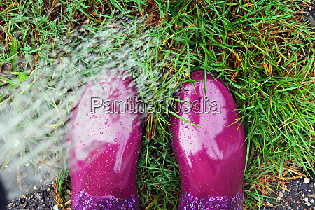 a woman with rubber boots watering