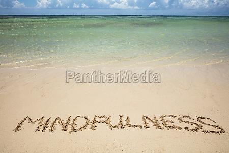 mindfulness texto escrito en la arena