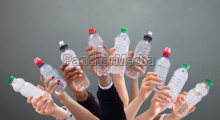 diferentes personas sosteniendo botellas de agua