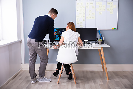 two businesspeople analyzing graph on computer