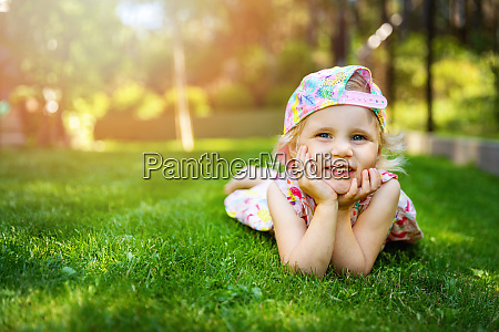 little girl laying on green grass