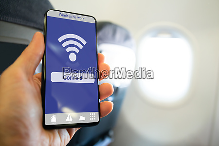 persons hand holding mobile phone showing