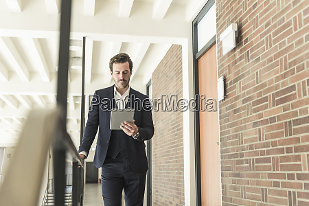 young businessman standing on gallery in