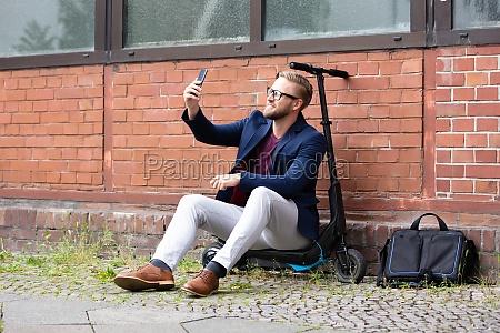 hombre sentado en scooter electrico haciendose