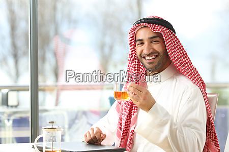 hombre arabe feliz sosteniendo una taza