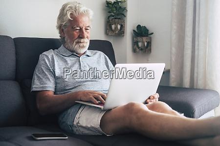 hombre mayor usando portatil en el