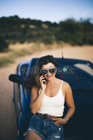 mujer sexy apoyada en convertible usando