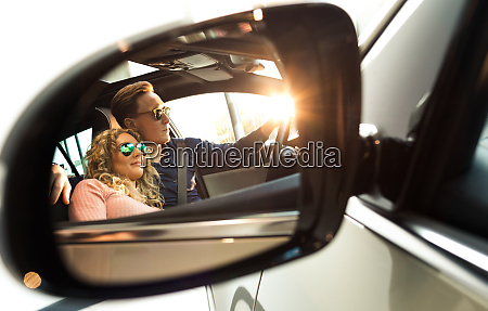 couple reflecting in sideview mirror of