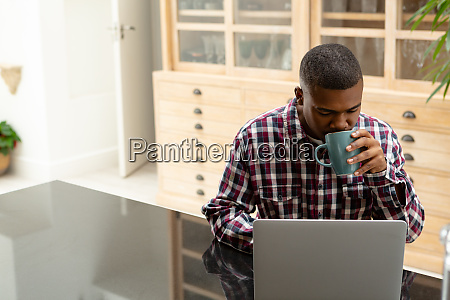 man drinking coffee while using laptop