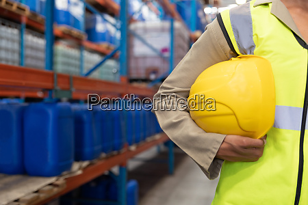 female worker holding hard hat in
