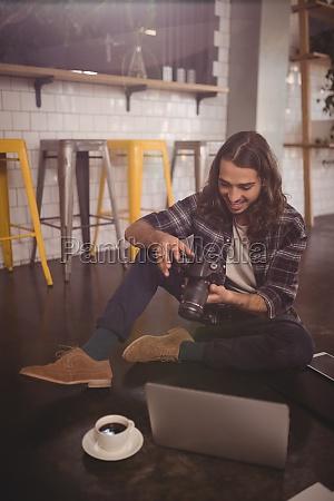 smiling young man using dslr camera