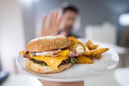 hombre rechaza hamburguesa ofrecida por persona