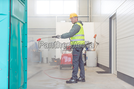 trabajador limpiando un banyo de alquiler