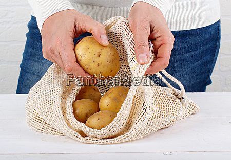 woman put fresh potatoes in a