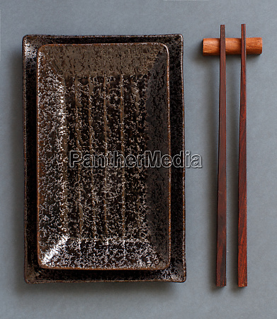 chopsticks and rectangular plates on dark