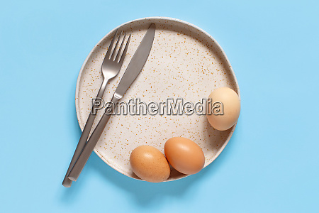 plate eggs fork and knife over