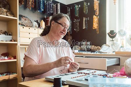 mujer trabajando en un collar de