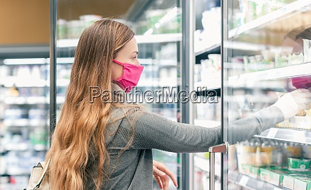 mujer en supermercado comprando en isla