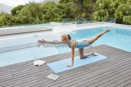 mujer joven practicando yoga cerca de