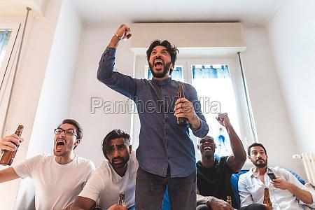 hombres viendo deporte en la television