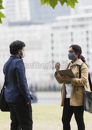empresarios con mascaras faciales hablando en